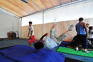 Ángel Trujillo helping other young people to do somersault at Ángeles D1 school