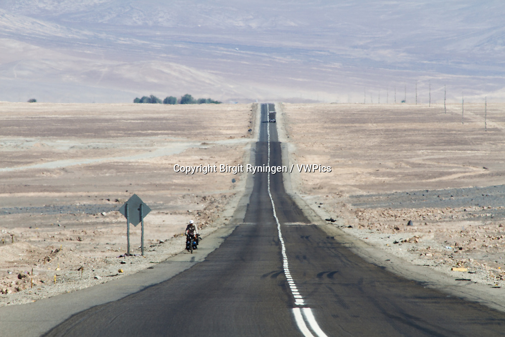 Long distance cyclist biking by Panamerican Highway through teh Atacama desert, Chile