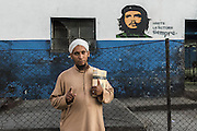 "Dawud in a suburb of Havana in front of a murale representing Che Guevara. His gesture with the index finger up means ""Allah is one""."