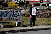 "A man stands on the corner of Broad and Central with a bible and sign preaching to passing cars. He is a member of one of the many churches that offer salvation in the ""Bottoms."""