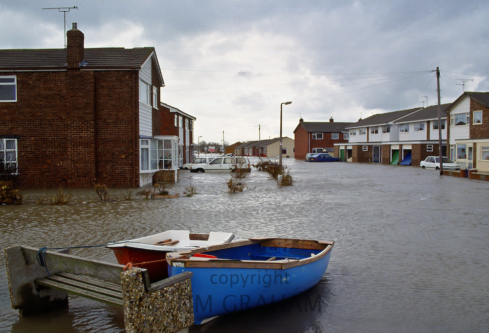 Boats tethered to a stone bench in the flooded town of Towyn in North Wales, UK.