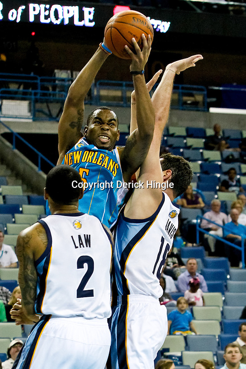 October 9, 2010; New Orleans, LA, USA; New Orleans Hornets guard Marcus Thornton (5) shoots over Memphis Grizzlies forward Josh Davis (18) and guard Acie Law (2) during the second half of a preseason game at the New Orleans Arena.The Grizzlies defeated the Hornets 97-90. Mandatory Credit: Derick E. Hingle
