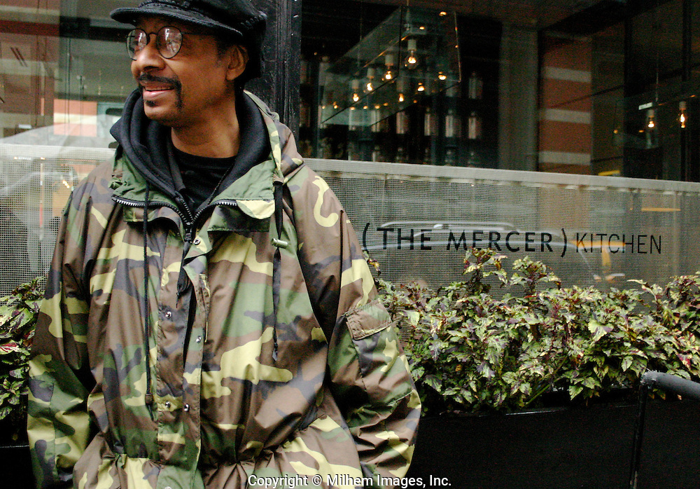 Man in camoflauge jacket stands beside greenery outside the Mercer Kitchen in SoHo NYC. The greenery resembles leaf lettuce. The jacket blends in with the leaves. I call this the Mercer Salad bar.
