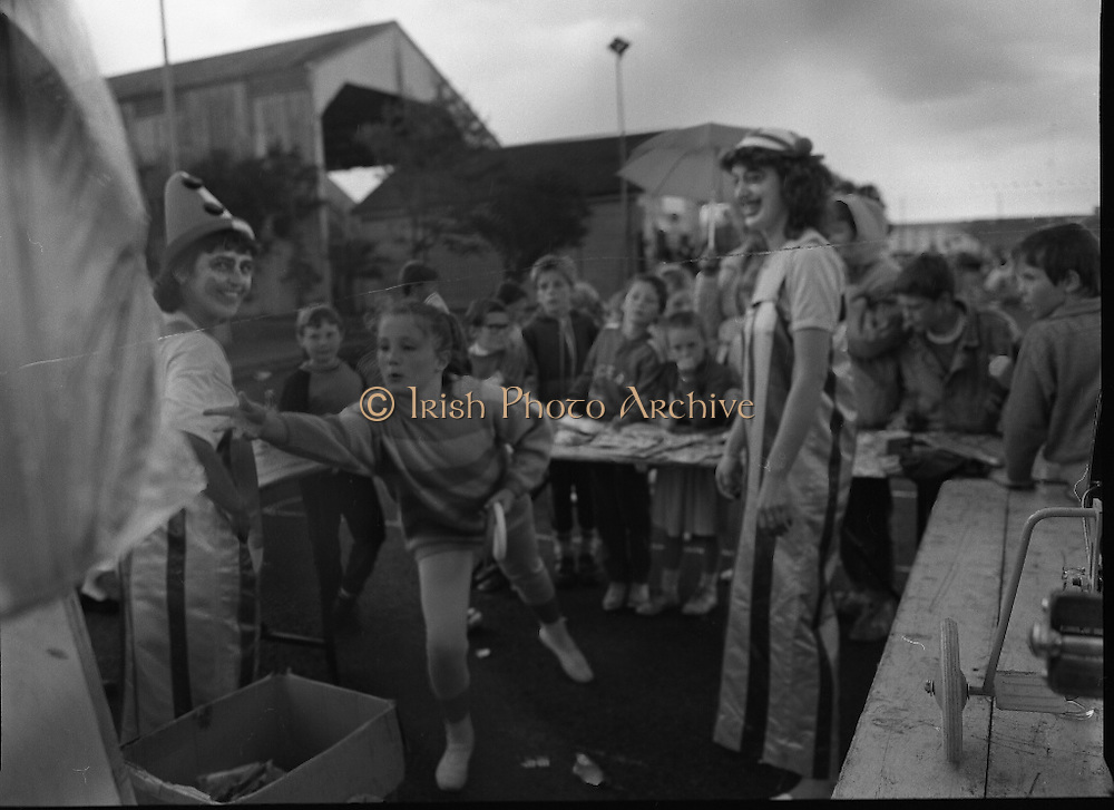 """Guinness Family Day At The Iveagh Gardens. (R83)..1988..02.07.1988..07.02.1988..2nd  July 1988..The family fun day for Guinness employees and their families took place at the Iveagh Gardens today. Top at the bill at the event were """"The Dubliners"""" who treated the crowd to a performance of all their hits. Ireland's penalty hero from Euro 88, Packie Bonner, was on hand to sign autographs for the fans...Image shows the concentration required by this young lady as she takes part in the ring tossing competition."""