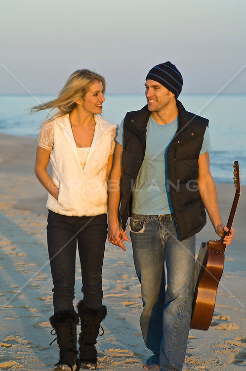 couple walking on the beach in jeans and vests while carrying a guitar