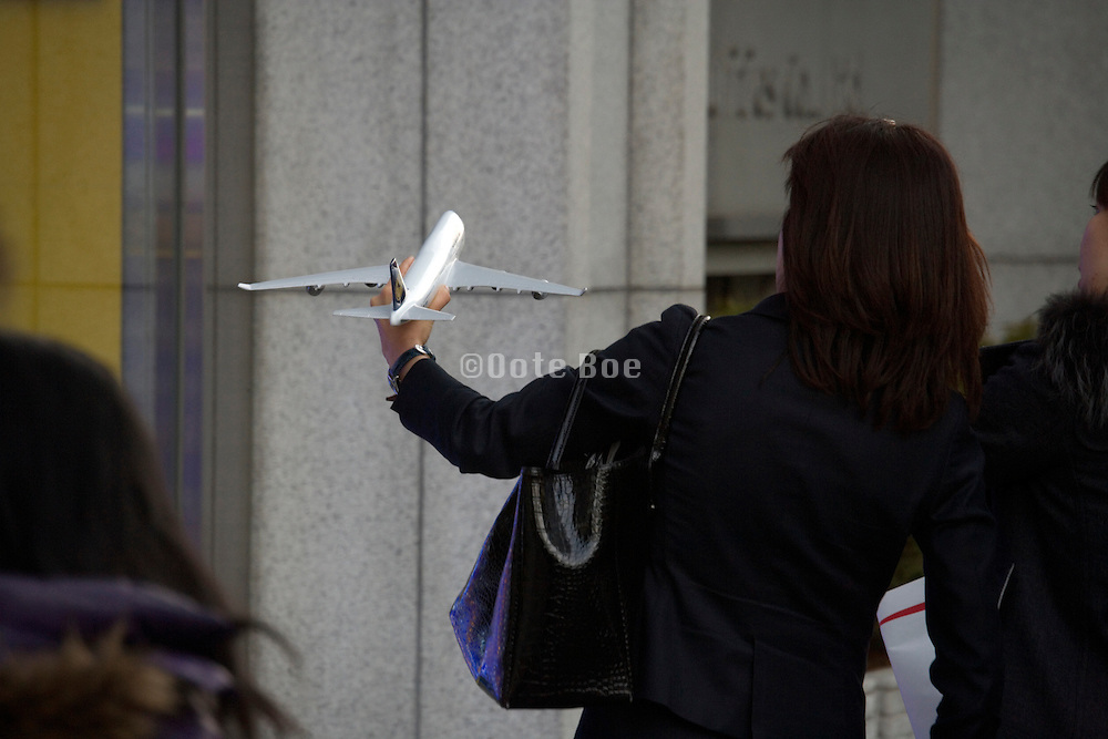 woman holding up small model passenger jumbo jet airplane