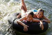 Two girls (7-9) lying on float tube elevated view.