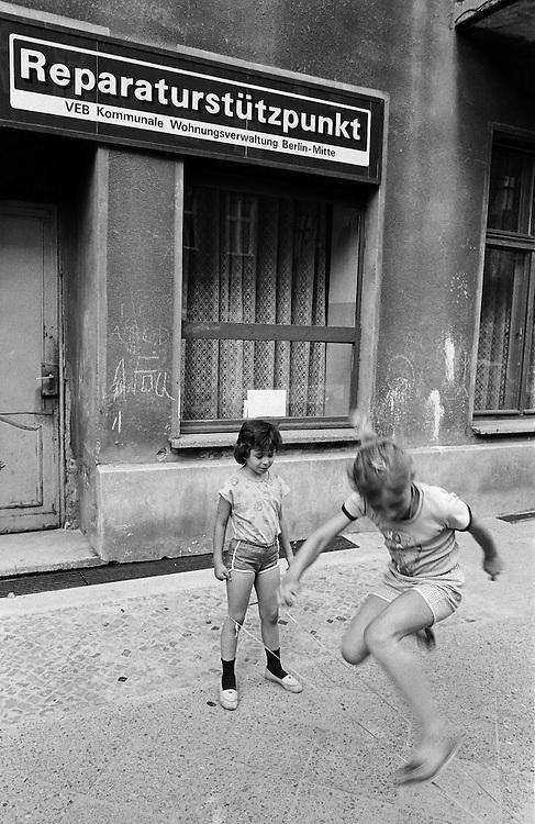 Deutschland - GERMANY - Mauerfall - 1990 -  Die Berliner Mauer verschwindet aus dem Stadtbild, die Mauer wird abgerissen/abgetragen : HIER: Kinder spielen Gummitwist vor einem DDR-Reparaturstützpunkt in Berlin-Mitte, 08/1990.1990 - FALL OF THE BERLIN WALL - the wall disappears, is demolished; HERE: Kids playing in front of a GDR repair outlet in Berlin-Mitte 08/1990.copyright: Christian Jungeblodt