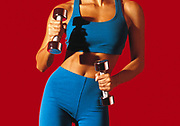 Woman in blue exercise shorts and top exercising with shiny dumbbells in front of bright red background. Shoulders to thighs crop