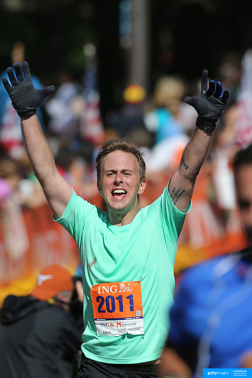 The Finish Line. Expressions of agony and ecstasy on the faces of athletes as Andrew Stinger, Menlo Park, finishes the ING Hartford Marathon, Bushnell Park, Hartford. Connecticut. USA. Hartford, Connecticut, USA. 12th October 2013. Photo Tim Clayton
