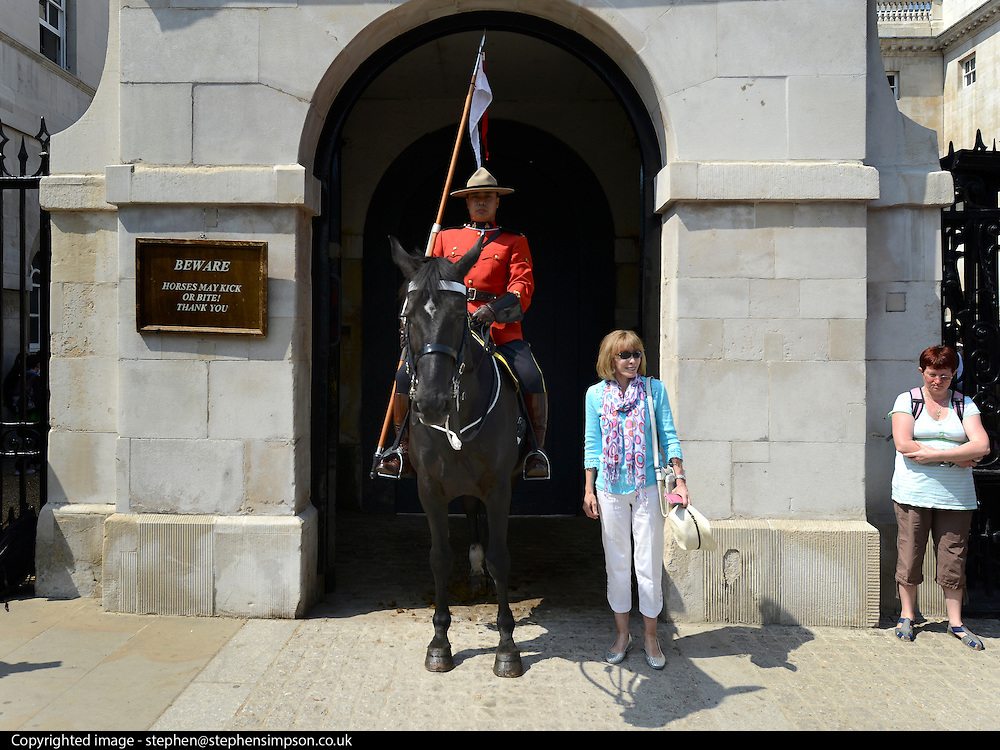 © Licensed to London News Pictures. 23/05/2012. London, UK A tourist has her picture taken alongside Constable Davis Tsui in position on Whitehall. Canadian Mounties Guard Her Majesty the Queen at Horse Guards Parade on Whitehall in Westminster. They will guard on all day and will be the first non-British force to guard the Queen. Photo credit : Stephen Simpson/LNP