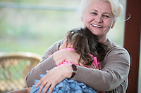 Portrait of happy grandmother hugging granddaughter in house