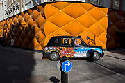 A black London cab with door advertising drives past the temporary renovation hoarding of luxury brand Louis Vuitton in New Bond Street, on 25th February 2019, in London, England.