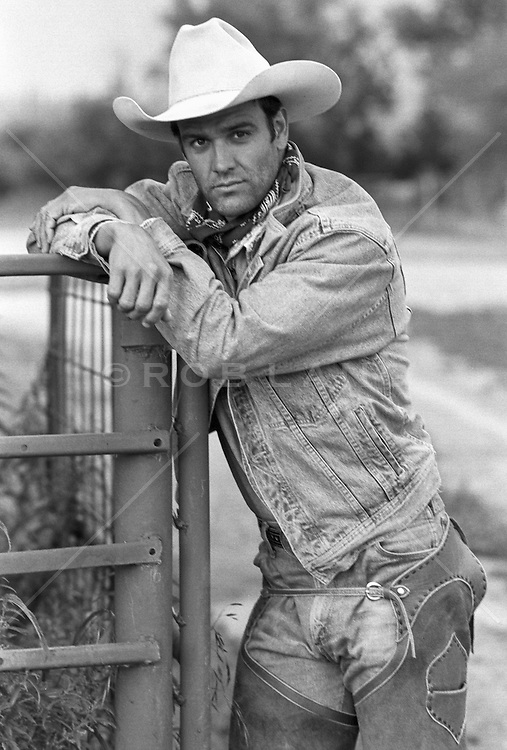 sexy cowboy leaning on a fence on a ranch