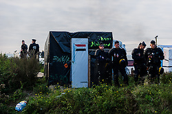 October 25, 2016 - Calais, France - Police officers stand during the eviction of the Calais Jungle between tents  in Calais, France, on 25 October 2016. Up to the evening, about 4,000 migrants from the Refugee camp on the coast at the English Channel were distributed to several regions in France. The police have begun to tear down the huts and tents in the camp. (Credit Image: © Markus Heine/NurPhoto via ZUMA Press)