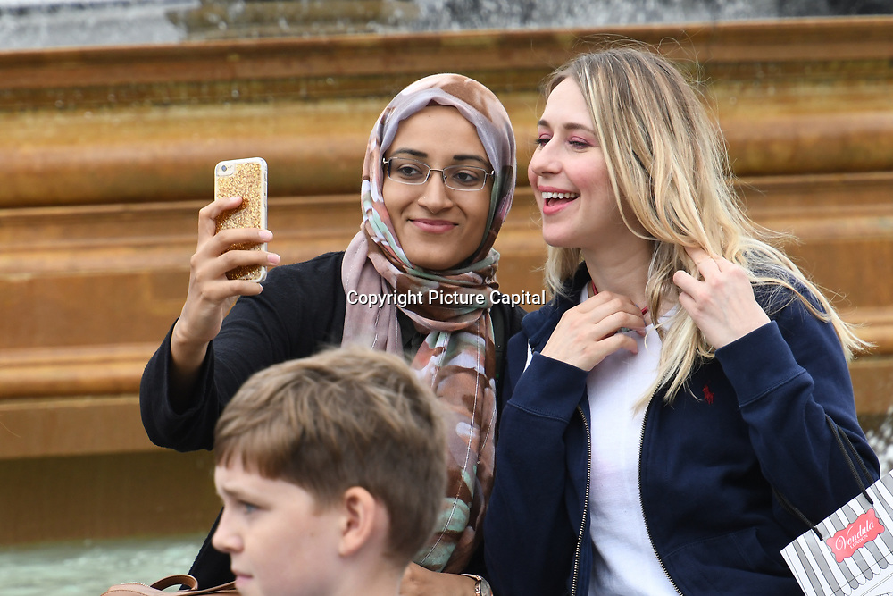 A muslim lady and a white taking a selfies in Trafalgar square on 18 August 2018, London, UK.