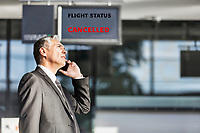 Mature businessman making report on his cancelled flight while standing at his boarding gate in airport