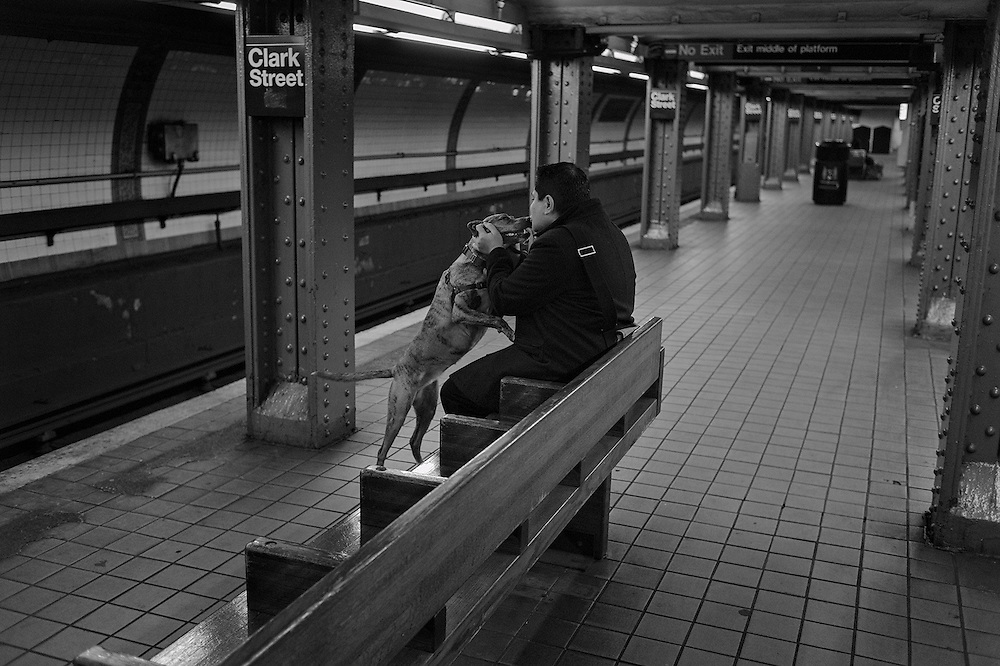 Man kissing dog while waiting for subway, Brooklyn, NY, US