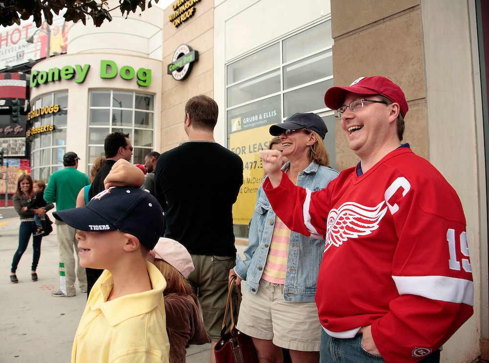 Andy Vogel, right, of Claremont, Calif., waves to a Los Angeles County Sheriffs deputy who wondered what the event was as he waits in line with his wife Sara Vogel, center, and kids Ben, 9, bottom left, and Maddiy, 6, bottom center, for the opening of Coney Dog, a Detroit-style Coney Island hot dog restaurant, on Sunset Boulevard in West Hollywood, Calif., Saturday, June 19, 2011. Andy Vogel is originally of Grosse Pointe, Mich. (AP Photo/Jason Redmond)