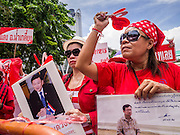 19 MAY 2013 - BANGKOK, THAILAND:   Red Shirts hold photos of ousted and exiled Thai Prime Minister Thaksin Shinawatra during a Red Shirt rally in Ratchaprasong Intersection honoring Red Shirts killed by the Thai army in 2010. More than 85 people, most of them civilians, were killed during the Thai army crackdown against the Red Shirt protesters in April and May 2010. The Red Shirts were protesting against the government of Abhisit Vejjajiva, a member of the opposition who became Prime Minister after Thai courts ruled the Red Shirt supported government was unconstitutional. The protests rocked Bangkok from March 2010 until May 19, 2010 when Thai troops swept through the protest areas arresting hundreds.  PHOTO BY JACK KURTZ