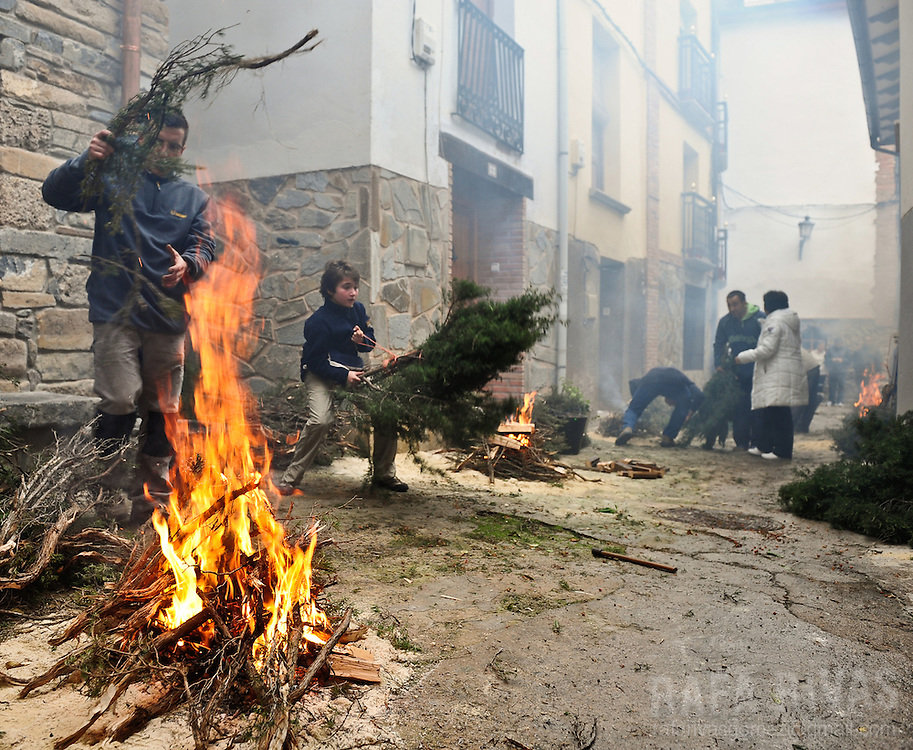 """People take part during the """"Procession of smoke"""" on November 25, 2012, in the northern Spanish village of Arnedillo. Locals light bonfires to produce smoke that covers Arnedillo streets while the patron saint San Andres is carried in procession."""