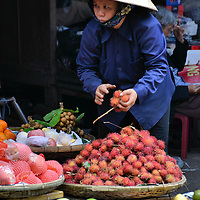 Woman Wearing Nὀn Lá Conical Hat Holding Rambutan in Nha Trang, Vietnam<br /> The circular-coned, conical hat has been worn by Southeast Asia farmers, laborers and market vendors like this woman selling rambutan fruit in Nha Trang, for over 3,000 years.  In Vietnam, they are called nὀn lá which means leaf hat.  Please, never call them a coolie hat because this is very offensive.  They are still commonly worn to protect from the sun, heat and rain.