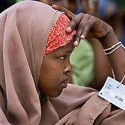 A young Somali refugee waits with her ration card to receive food at the Hagadera refugee camp in Dadaab, Kenya.