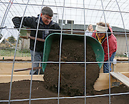 George Harper (from left) of Independence and Carolyn Koopman of  Garnavillo pour a load of dirt into the planter during a Hoop House and Root Zone Heating Workshop at Prairiewoods in Hiawatha on Saturday October 6, 2012.