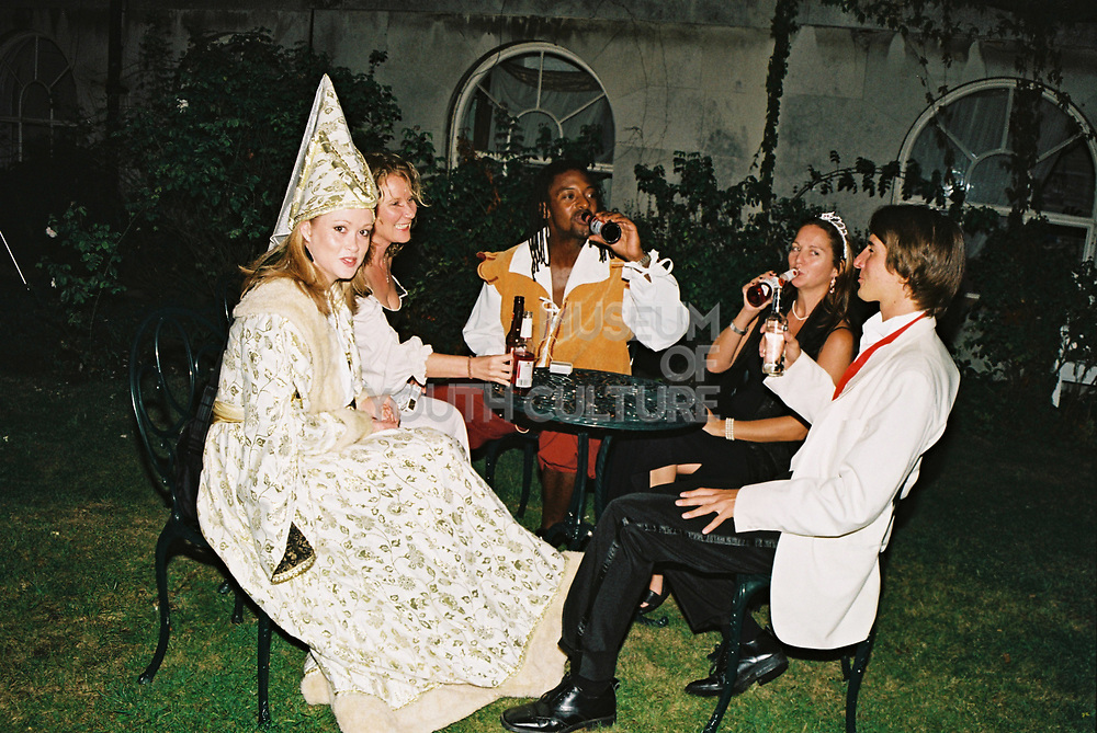 Group in historical fancy dress costumes drinking outside at a table in the garden, Posh at Addington Palace, UK, August, 2004