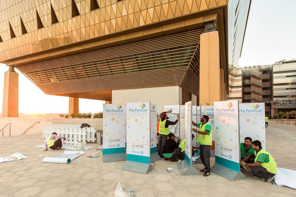 ABU DHABI, EMIRATS ARABES UNIS - 20 JANVIER 2016: Un groupe de travailleurs préparent des panneaux pour les animations durant le 'Abu Dhabi Sustainability Week' à Masdar City.