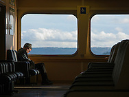 man sitting alone sleeping on ferry in window