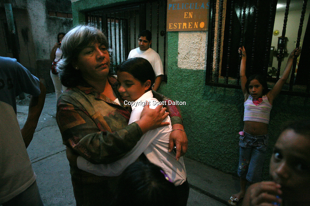 Maibel Troia, left, the director of the Don Bosco Center, a music center in the poor barrio of Chapellin, is hugged by one of her students Stephany Rodriguez, 12, on November 9, 2006. The Venezuelan government sponsors the National System of Youth and Children's Orchestras of Venezuela, which provides instruments and music training to the countries youths. The program was founded 31 years ago and has over 250,000 children participating throughout the country. (Photo/Scott Dalton)