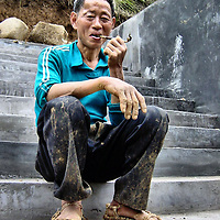 Tujia Peapod Boat Worker Smoking Pipe near Shennong Stream on Yangtze River, China<br /> The Yangtze River flows through China for nearly 4,000 miles.  Before the Shennong Stream empties into the Yangtze near the Wu Gorge, it zigzags from atop the Shennong Jia peak through narrow passages, lush vegetation, spectacular canyons, waterfalls and rocky shores.  The peasants that navigate these treacherous waters are called Tujia.  They expertly steer their sampans (called peapod boats) using primitive, long paddles or, when stuck in the shallows, they drag the boat by rope.  This Tujia man was taking a break for a smoke on his opium pipe.