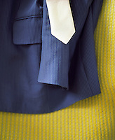Suit and Tie on Bed with yellow cover close-up