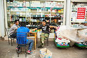 14 MARCH 2013 - ALONG HIGHWAY 13, LAOS: Chinese men relax in front of a Chinese pharmacy in the Chinese market near the end of Highway 13 in the Boten Special Economic Zone. The SEZ is in Laos immediately south of the Lao Chinese border. It has turned into a Chinese enclave but many of the businesses struggle because their goods are too expensive for local Lao to purchase. Some of the hotels and casinos in the area have been forced to close by the Chinese government after reports of rigged games. The paving of Highway 13 from Vientiane to near the Chinese border has changed the way of life in rural Laos. Villagers near Luang Prabang used to have to take unreliable boats that took three hours round trip to get from the homes to the tourist center of Luang Prabang, now they take a 40 minute round trip bus ride. North of Luang Prabang, paving the highway has been an opportunity for China to use Laos as a transshipping point. Chinese merchandise now goes through Laos to Thailand where it's put on Thai trains and taken to the deep water port east of Bangkok. The Chinese have also expanded their economic empire into Laos. Chinese hotels and businesses are common in northern Laos and in some cities, like Oudomxay, are now up to 40% percent. As the roads are paved, more people move away from their traditional homes in the mountains of Laos and crowd the side of the road living off tourists' and truck drivers.    PHOTO BY JACK KURTZ