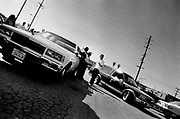 Gang members hanging out with their cars outside a Taco Bell, East Central LA, USA, 1990's