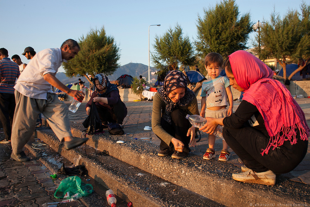 Refugees that spent the night at the port, using bottles with watter to wash themselves.<br /> The port of Mytilene where many refugees stay while they apply for a permit to stay in Greece or while they are waiting to board the ferry to Athens.