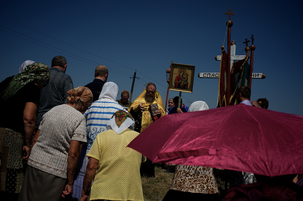 Locals attend a religious ceremony at the Malaysia Airlines MH17 crash site in Grabovo, a small rural village in the province of Donetsk, eastern Ukraine. Malaysia Airlines flight MH17 was travelling from Amsterdam to Kuala Lumpur when it crashed killing all 298 on board including 80 children. The aircraft was allegedly shot down by a missile and investigations continue over the perpetrators of the attack.