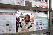 Man reading newspaper at street stall in Brickaville, Madagascar. August 2014<br /> Photo:&copy; Zute Lightfoot