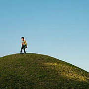 A boy plays atop a burial mound in Tumuli Park, a UNESCO World Heritage site in Gyeongju, South Korea.