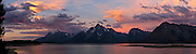 At Jackson Lake, sunrise illuminates clouds with orange, pink, and magenta light. Grand Teton National Park contains the major peaks of the 40-mile (64 km) Teton Range and part of the valley known as Jackson Hole, in Wyoming, USA. A parkway connects 10 miles north to Yellowstone National Park. Surrounding parkland and National Forest constitute the Greater Yellowstone Ecosystem, one of the largest intact mid-latitude temperate ecosystems in the world. Five overlapping images were stitched to make this panorama.