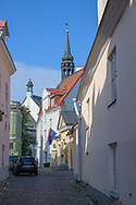 Tallinn, Estonia -- July 23, 2019. A photo looking down a side street in Tallin, Estonia; St Mary's Cathedral is in the background.