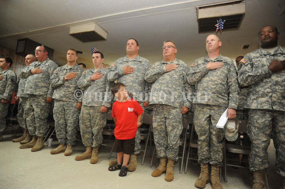 Silas Knight (foreground) stands in front of his dad Josh Knight during the 289th Engineer Battalion send off ceremony in Water Valley, Miss. on Sunday, May 6, 2012.