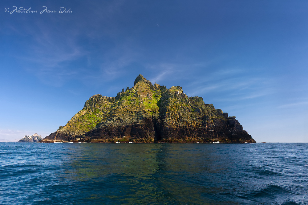 Skellig Michael from the sea with the Old Lighthouse and the South Peak and a clear blue sky day with a reflexion on the calm Atlantic sea, County Kerry, Skellig Coast, Skellig Ring, Ireland.<br />