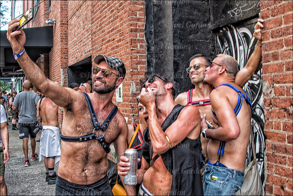 Selfie at Folsom Street East, phone held at arm's length, made for services such as Facebook, Instagram , Snap Chat and Twitter. They are usually flattering and made to appear casual.<br /> <br /> Folsom Street East the S&amp;M Bondage adult-themed Folsom Street East, New York&rsquo;s  s/m-leather-fetish themed street festival.
