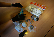 A prison officer examines confiscated items for drugs at HMP Liverpool, also known as Walton Prison. The prison was given a scathing report in 2017 which pointed out various failings and problems. Present governor Pia Sinha was appointed in that year and in the next two years she turned the prison around with a programme of improvements and support for inmates and infrastructure. HMP Liverpool houses a maximum of 700 prisoners with an overall staff of around 250.