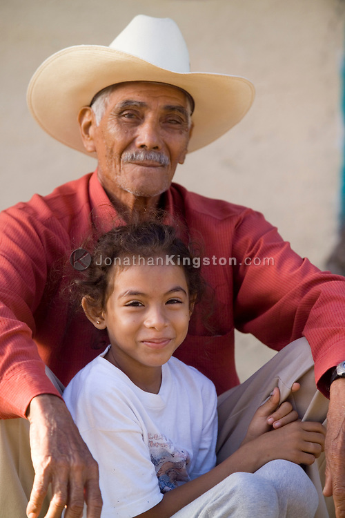 A young girl and her grandfather sit and rest during festivities honoring the week of their patron saint in Somotillo, Nicaragua. Every town and city in Nicaragua holds annual celebrations for its patron saint. Celebrations in Somotillo included Nicaraguan bull fighting, horse parades, a carnival, and other events. <br /> Like other towns in northwestern Nicaragua, many residents are part of the FSLN party, commonly known as Sandinista.