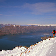 A skier on top of Mount Albert on Minaret Station, Wanaka, with Lake Wanaka in the background. Wanaka, Queenstwon Lake District, South Island, New Zealand. Photo Tim Clayton