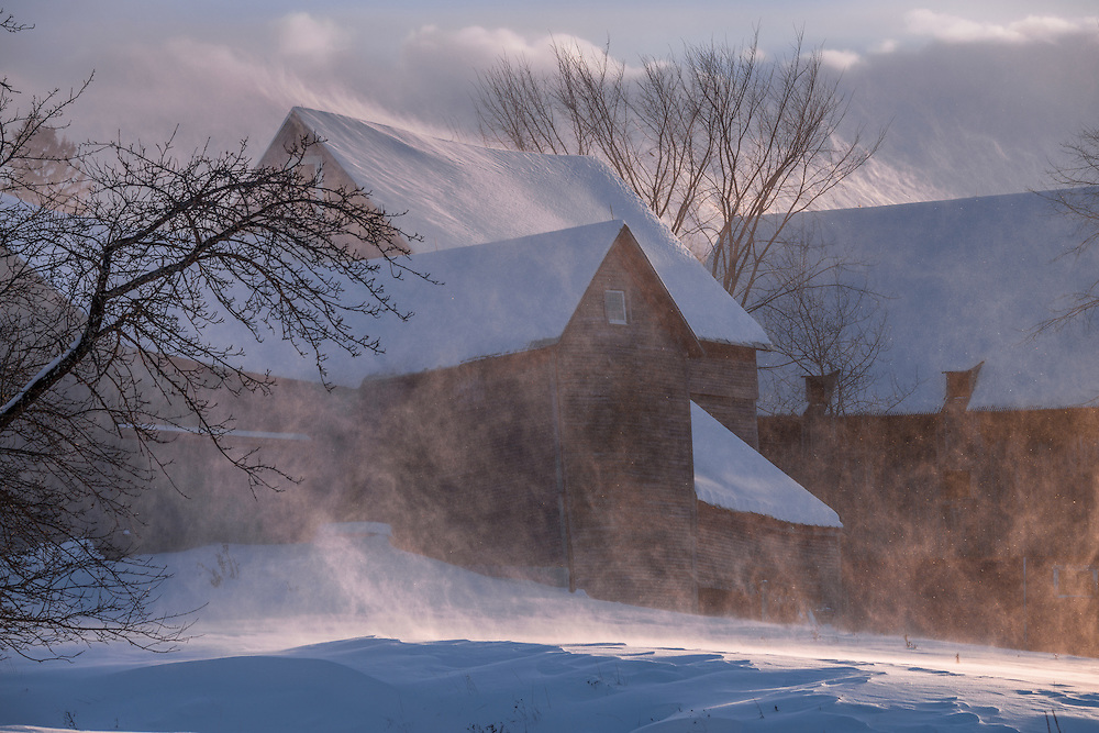 Sunlight on wind blown snow of field & weathered barns in winter, Hartford, VT