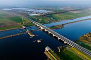 Nederland, Flevoland, Overijssel, Noordoostpolder, 04-11-2018. Ramspolbrug met N50, over de vaargeul het Ramsdiep. Naast de brug de balgstuw, onderdeel van Waterkering Kampen, tussen Ketelmeer en Zwarte Water (voorgeond). De balgstuw is een stormvloedkering en bestaat uit een opblaasbare dam of dijk, opgebouwd uit drie balgen. In niet-opgeblazen toestand liggen de balgen op de bodem. <br /> Ramspol bridge and Ramspol barrier, inflatable dike, between Ketelmeer and Black Water. The Balgstuw (bellow barrier) is a storm barrier and consists of an inflatable dam or dyke, composed of three bellows. Usually, each bellow rests on the bottom of the water.<br /> luchtfoto (toeslag op standaard tarieven);<br /> aerial photo (additional fee required);<br /> copyright&copy; foto/photo Siebe Swart